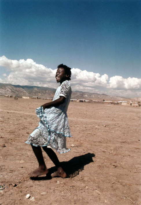 Young girl dancing in her blue lace dress belies the sinister poverty and violence that resides in the dusty dried out streets of Rabato, a slum just outside Gonaives, Haiti. Rabato is a scene of regular political protest and is thus the target of numerous slaughters and attacks on its citizens. 1990